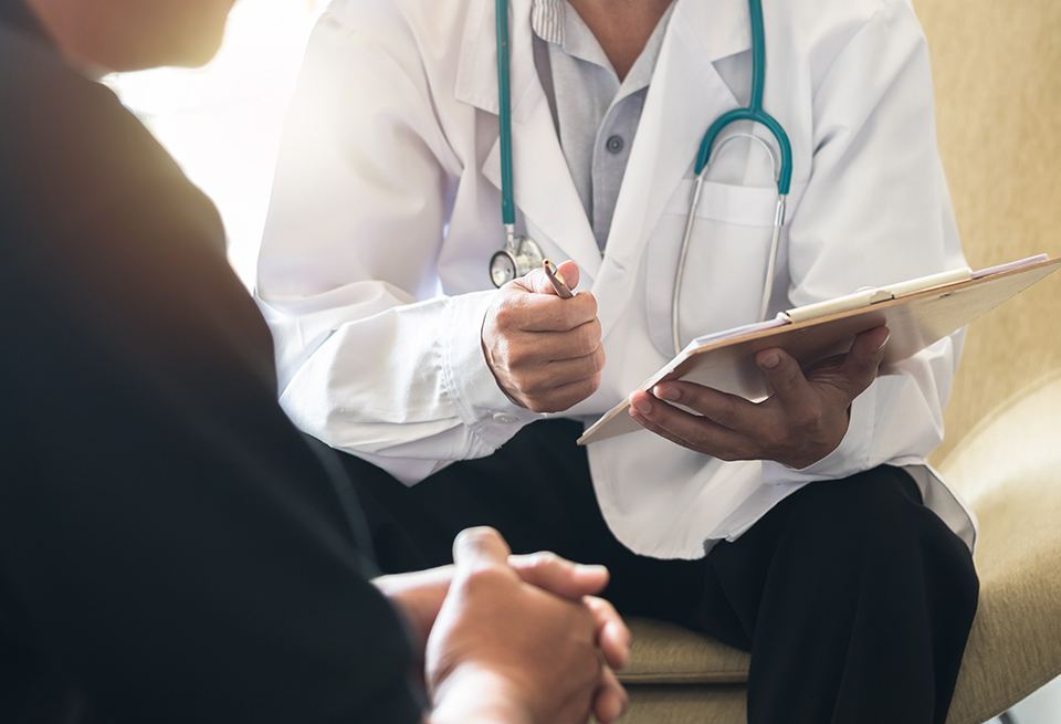 A doctor holding a clipboard and pen talks to a male patient.