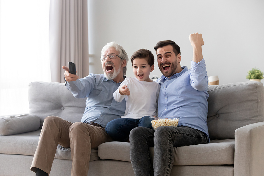 Photo of three males—child, middle aged, and elderly—cheering in reaction to TV