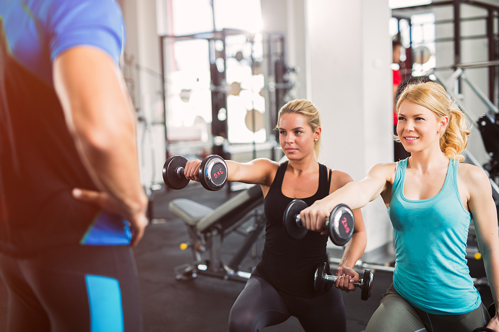 Two young women are exercising lunges with handheld weights at the gym. The personal trainer is monitoring them.